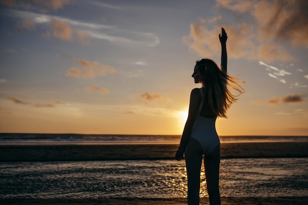 Caucasian woman wears white swimsuit in vacation. carefree young lady enjoying evening at ocean and looking at beautiful sunset.