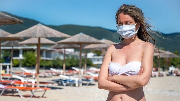 La donna caucasica in maschera medica bianca con le mani incrociate in costume da bagno su una spiaggia di asprovalta, grecia