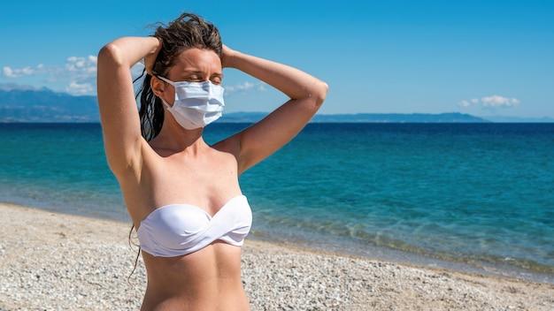 La donna caucasica in bianco maschera medica con le mani alzate alla testa e gli occhi chiusi in costume da bagno su una spiaggia di asprovalta, grecia