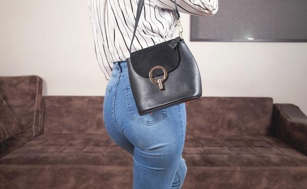 自宅で黒いバッグを持つ白人女性。