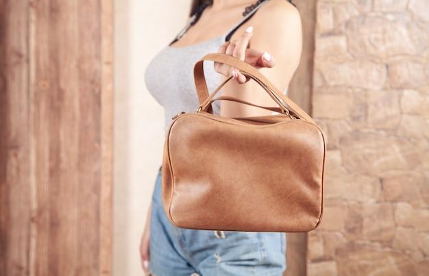 自宅で茶色のバッグを持つ白人女性。
