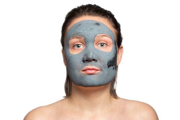 白い背景の上の彼女の顔に粘土または泥マスクを持つ白人女性。