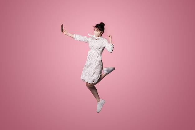 ピンクのスタジオの壁にジャンプしながら、医療マスクを持つ白人女性がドレスを着て、電話を使用して自分撮りを作っています