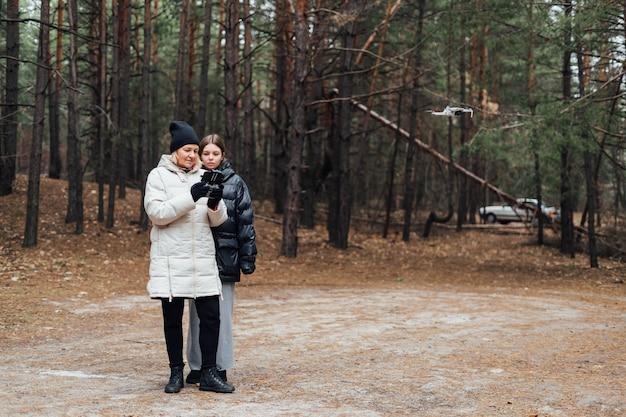 가 숲에서 공중 무인 항공기를 비행하는 성인 딸과 함께 백인 여자.