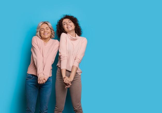 Кавказская женщина со светлыми волосами и ее кудрявая подруга восхитительно позируют на синей стене со свободным пространством