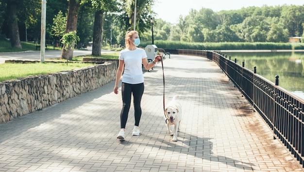 금발 머리와 그녀의 황금 강아지와 함께 산책하는 얼굴에 의료 마스크 백인 여자