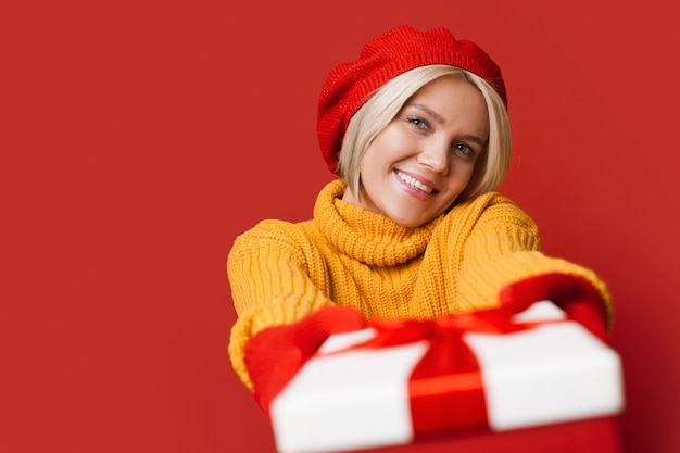 Caucasian woman with blonde hair wearing a nice hat is giving at camera a present box smiling and advertising something on a red studio wall