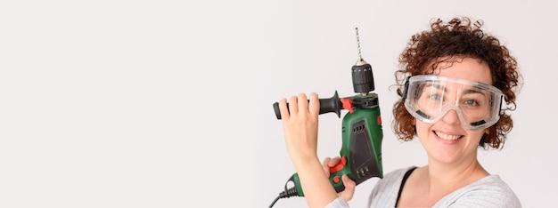 곱슬 머리를 가진 백인 여자는 홈 개선을 할 준비가 그녀의 손에 드릴을 보유하고 있습니다.
