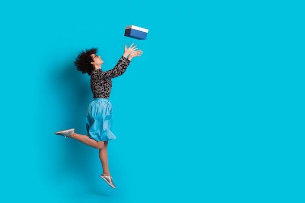 Кавказская женщина с вьющимися волосами ловит подарок на синей стене студии в платье и улыбается возле свободного места