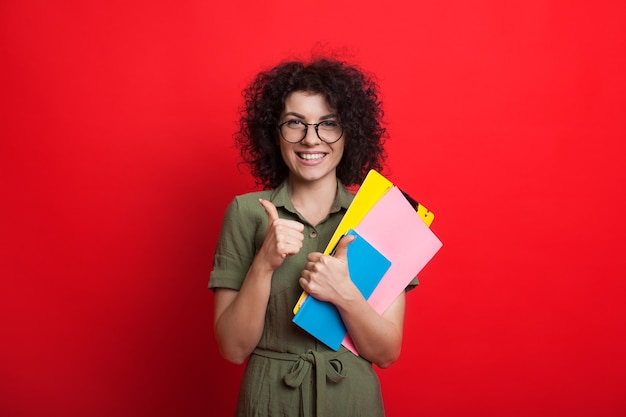 Caucasian woman with curly hair is holding some books and gesturing the like sign while posing on a red wall