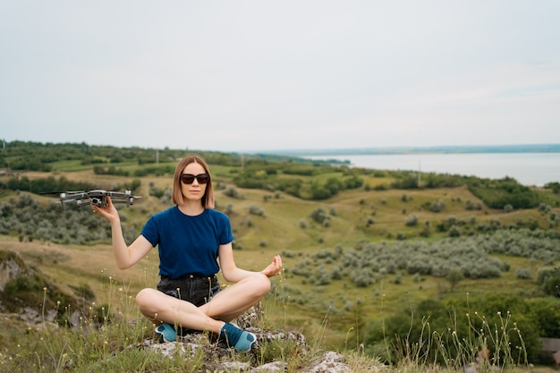 A caucasian woman with a drone in her hand, sitting on a green rocky hill with sky