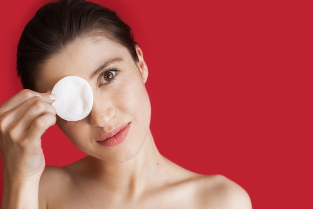 Caucasian woman with freckles covering her eye with a cotton disk posing with naked shoulders on a red  wall with free space