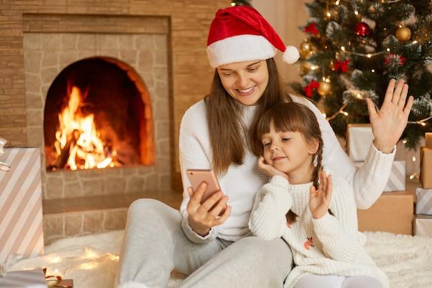 ビデオ通話をしているクリスマスに彼女の小さな娘と白人女性