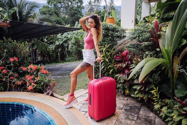 Кавказская женщина с большим розовым чемоданом на отдыхе в тропической стране