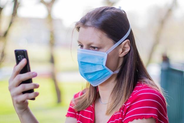 Кавказская женщина в маске смотрит на домашнюю террасу с помощью мобильного телефона во время карантина из-за пандемии коронавируса covid19.
