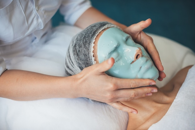 Кавказская женщина в медицинской шапочке проходит лечение лица, надевая маску в спа-салоне