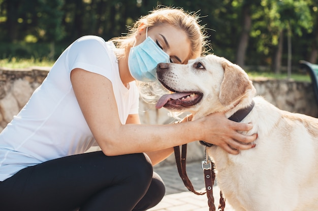 Caucasian woman with medical mask on face is embracing her golden retriever during a walk in park