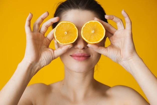 Кавказская женщина с обнаженными плечами позирует на желтой стене, покрывая глаза лимоном
