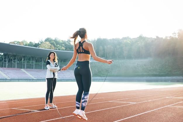 Кавказская женщина с личным тренером прыгает через скакалку как часть ее фитнес-тренировки спортивная женщина