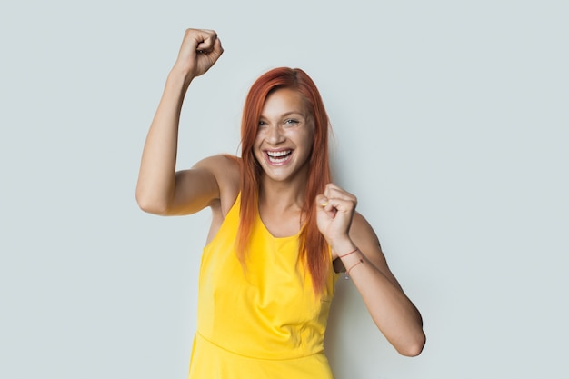 Caucasian woman with red hair is smiling and gesturing a win on a white wall in a dress