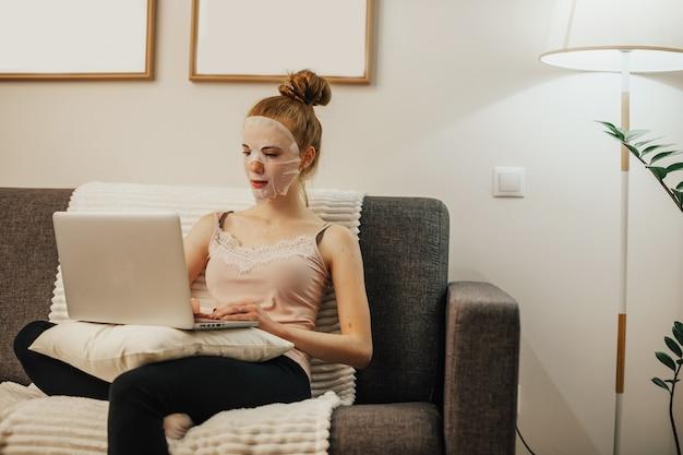 빨간 머리를 가진 백인 여자는 소파에 앉아 노트북을 사용하는 동안 그녀의 얼굴에 청소 마스크를 쓰고있다