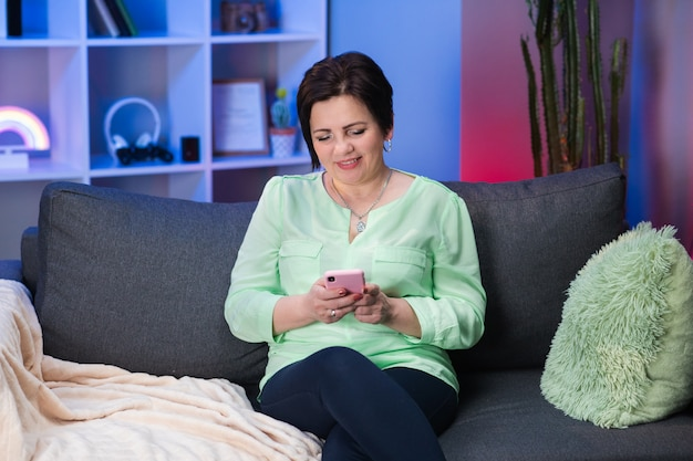 Caucasian woman with short black hair sitting on couch at home, holding invisible smartphone in hand and chatting with someone
