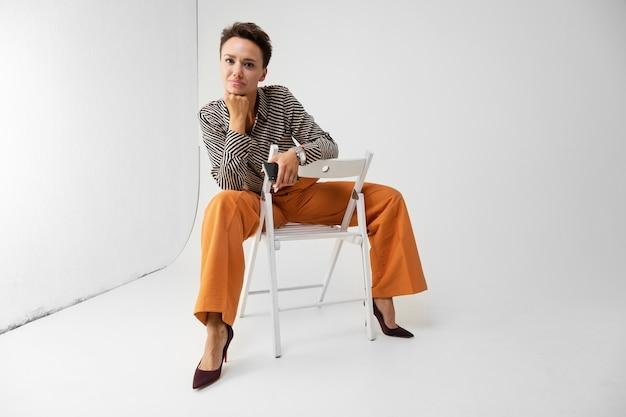 Кавказская женщина с короткими темными волосами, в красивом офисном костюме сидит на стуле со своим телефоном, изолированным на белом