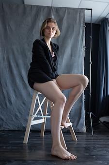 회색 패브릭 배경 앞의 자에 앉아 검은 정장 재킷에 짧은 머리를 가진 백인 여자