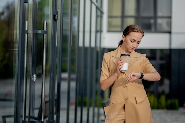 通りの建物の背景に立っているスマートフォンを持つ白人女性。