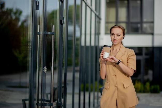 通りの建物の背景に立っているスマートフォンを持つ白人女性