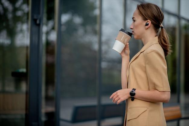 通りの建物に対して立っているスマートフォンを持つ白人女性