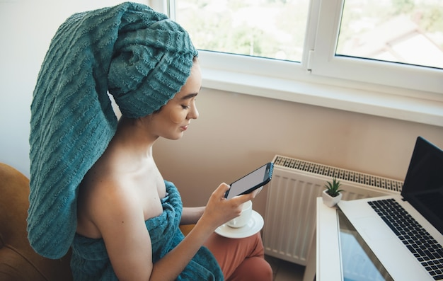 Caucasian woman with a towel on head is chatting on mobile and laptop at home after the bath