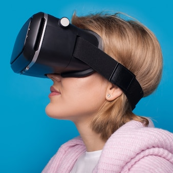 Caucasian woman with vr headset is posing on a blue  wall with free space