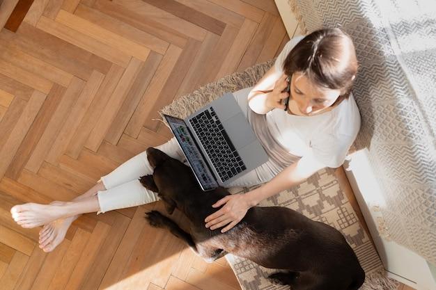 女性の隣で寝ている床のホームオフィスの犬に座っているラップトップで自宅で働く白人女性
