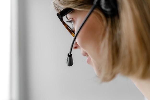技術サポートディスパッチャーがクローズアップを分離したようにビジネスの呼び出しに応答するヘッドセットで作業している白人女性