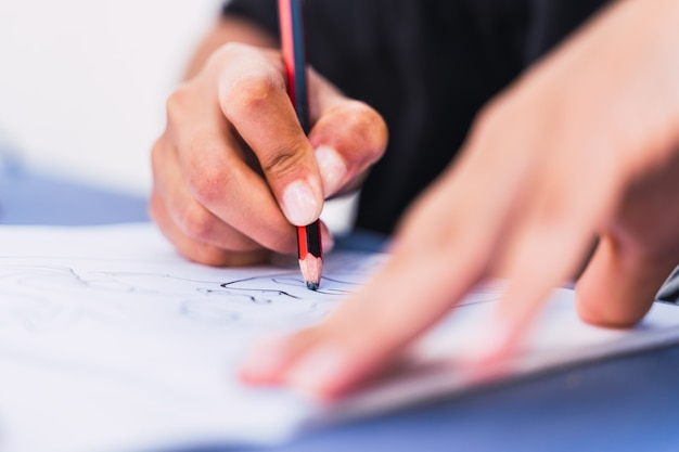 Caucasian woman writing and drawing in a notebook with a pencil