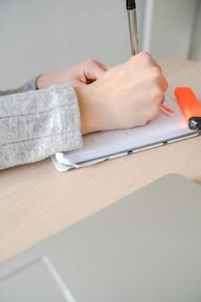 Кавказская женщина писать в блокноте с ручкой на своем столе на работе. пальма де майорка, испания