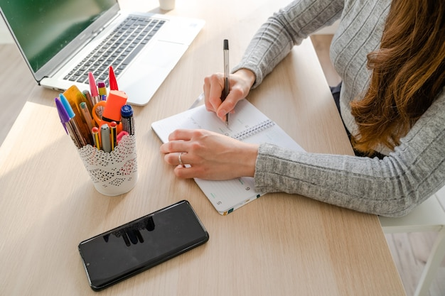 Caucasian woman writing in a notebook with a pen at her desk at work. palma de mallorca, spain