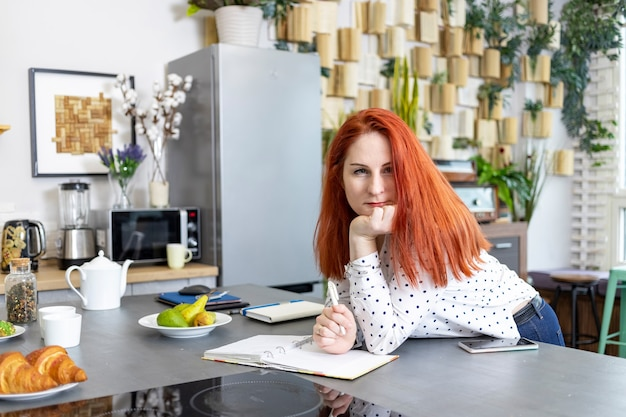 Caucasian woman writing in paper notebook on kitchen table at home beautiful woman write recipes