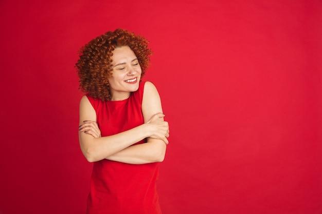コピースペースで赤い壁に分離された白人女性の肖像画