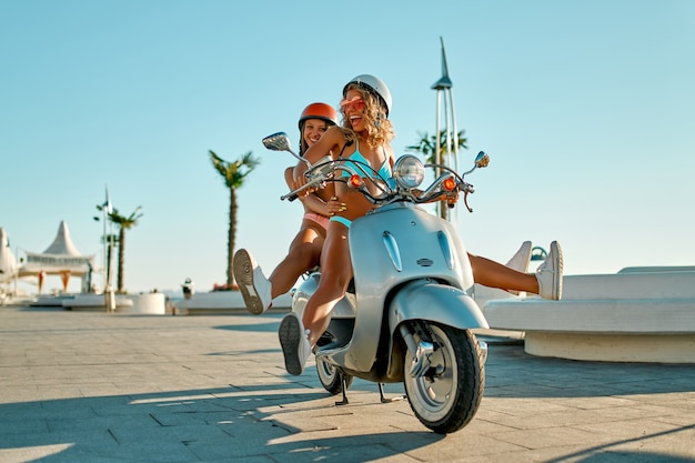 安全ヘルメットをかぶったビキニ水着を着た白人女性は、晴れた日にビーチ近くの自転車で楽しんでいます。