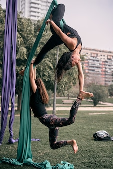 Caucasian women practicing some aerial silks difficult positions together in a city park