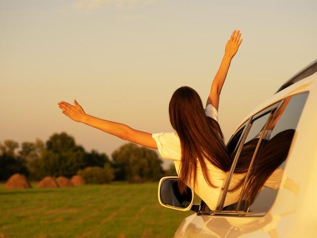 白人女性は休日にリラックスして旅行します。駐車場での旅行。自然と幸せに。夏に
