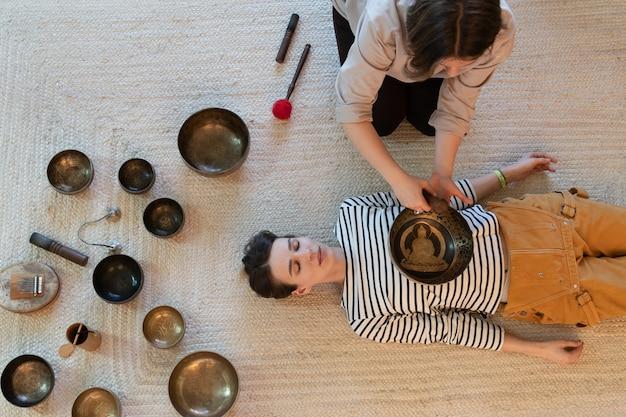 백인 여성은 마사지 치유 사운드 요법 대체 의학 개념에 노래 그릇을 사용합니다.