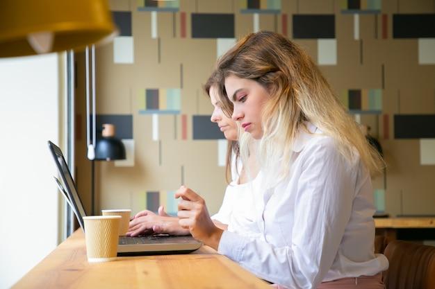 ノートパソコンで作業し、持ち帰り用のコーヒーを飲む白人女性