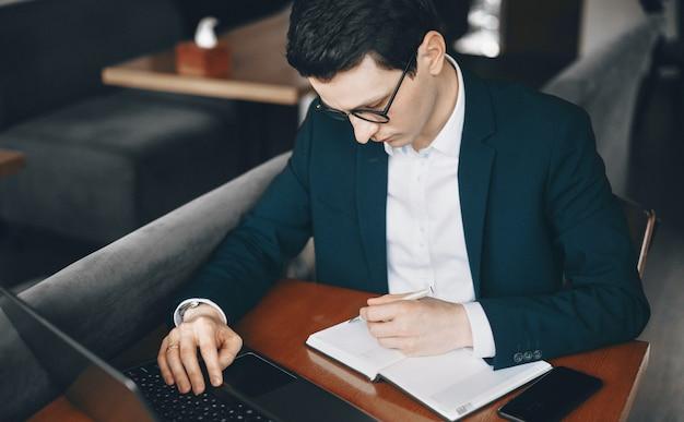 Кавказский рабочий, одетый в костюм, использует ноутбук, сидя в ресторане