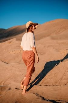 Кавказская молодая красивая девушка одна находится в горячем. закат в пустыне. девушка идет по золотому песку.