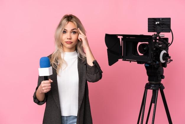 Кавказская молодая красивая женщина-репортер над розовой стеной