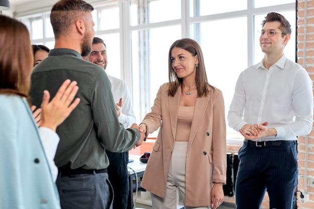 白人の若いビジネスマンの同僚の同僚がお互いに挨拶し、現代のオフィスで握手し、フォーマルな服を着た人々の側面図を持ち、パートナーシップを成功させています。スペースをコピーします。仕事