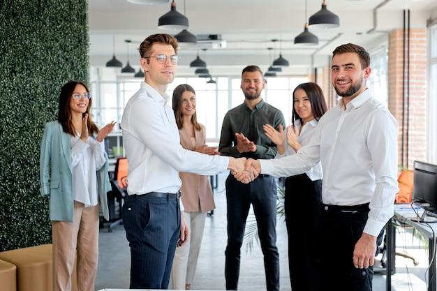 白人の若いビジネスマンの同僚の同僚がお互いに挨拶し、現代のオフィスで握手し、フォーマルな服を着た人々の側面図、成功したパートナーシップを持って、男性はカメラを見る